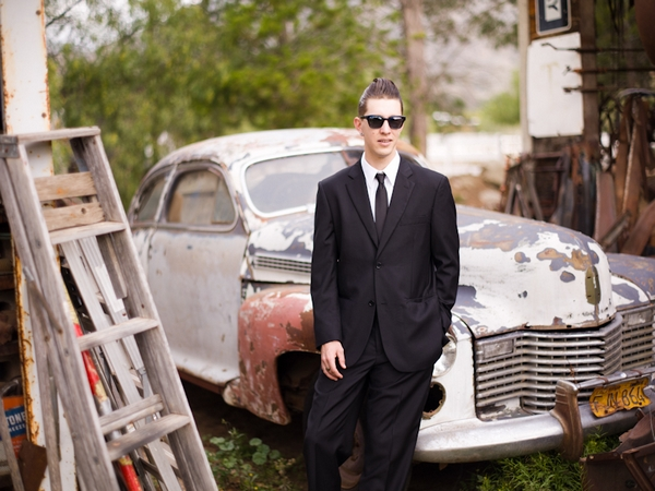 Groom standing in front of old car