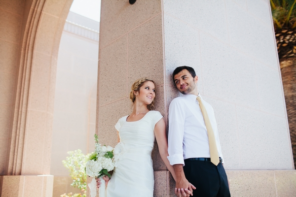 Bride and groom leaning back on pillar