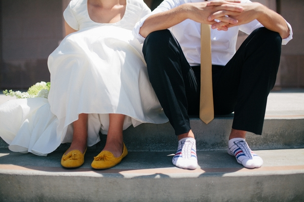 Bride and groom's legs as they are sat down