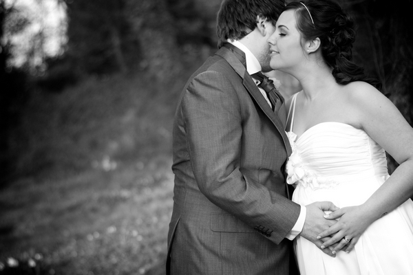 Groom with hand on bride's stomach - Picture by Karli Harrison Photography