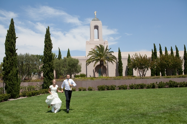 Bride and groom walking across grass at LDS Newport Beach Temple
