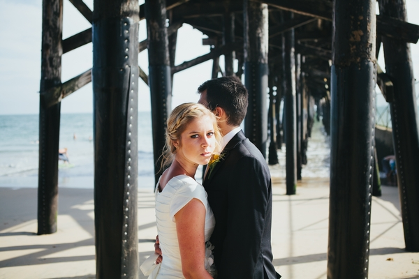 Bride and groom under pier