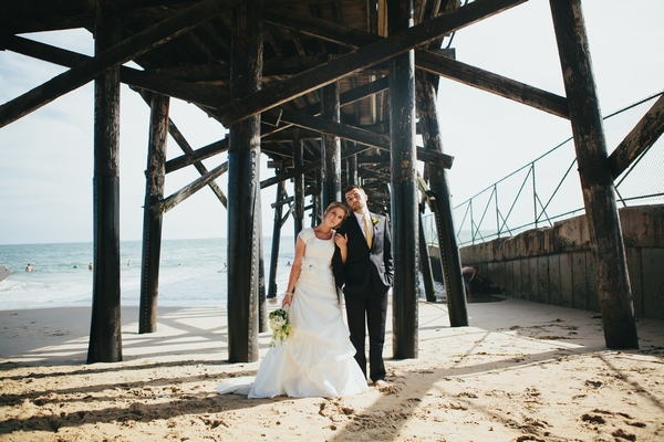 Bride resting head on groom under pier