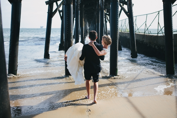 Groom carrying bride across sand