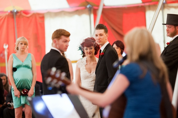 Bride and groom watching guitarist play during wedding ceremony