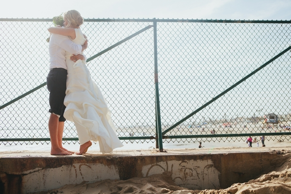 Bride and groom standing on step by beach