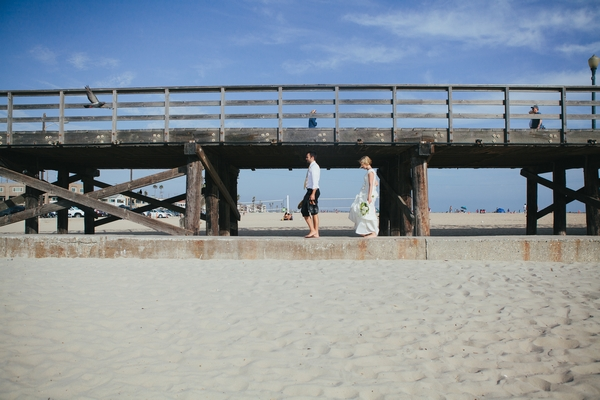 Bride and groom walking past pier