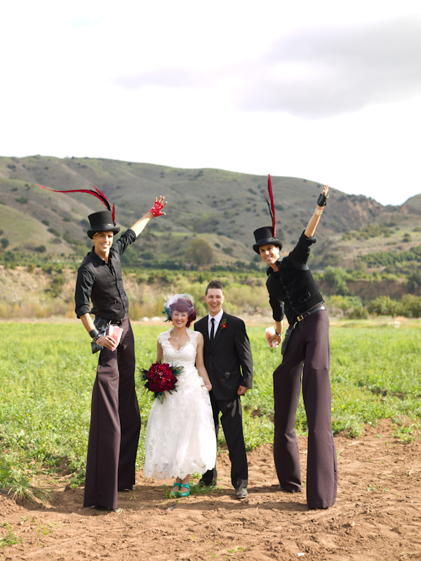 Bride and groom with circus performers on stilts