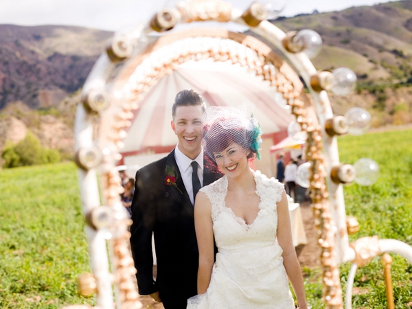 Bride and groom's reflections in circus mirror