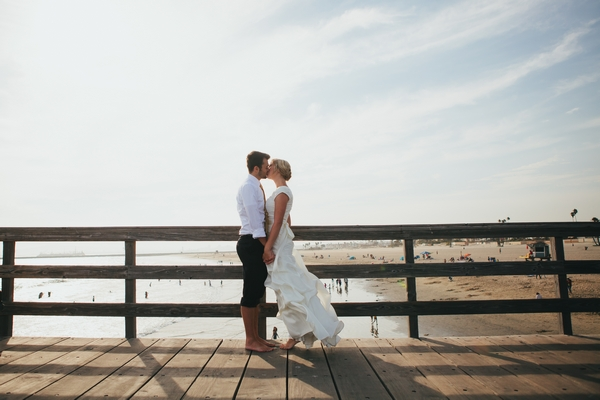 Bride and groom kissing on pier