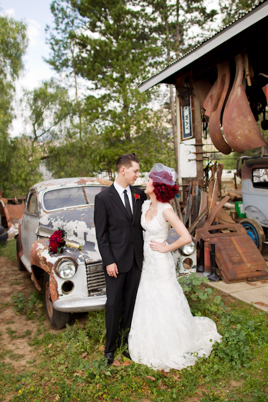 Bride and groom in front of old car