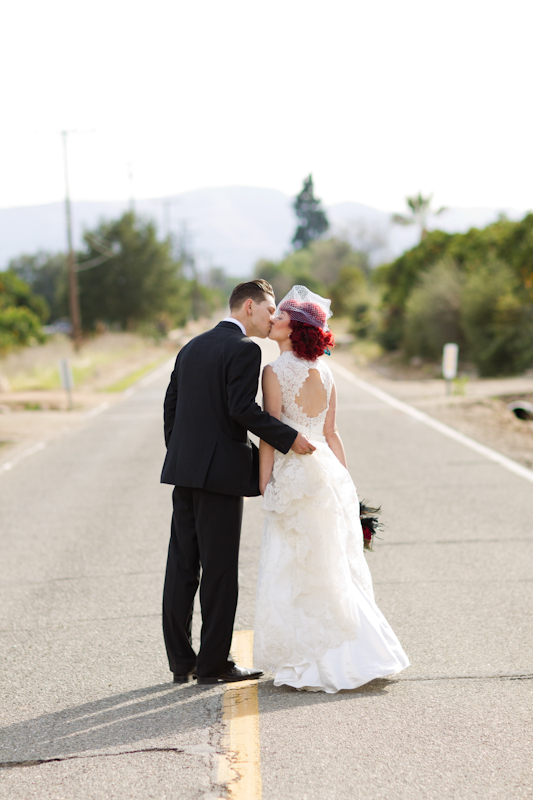 Bride and groom kissing in road