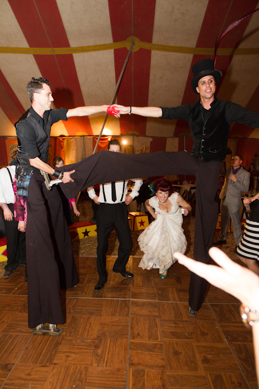Bride and groom about to go under circus performer's leg