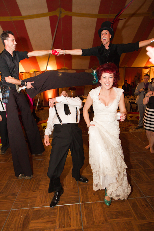 Bride and groom ducking under circus performer's leg