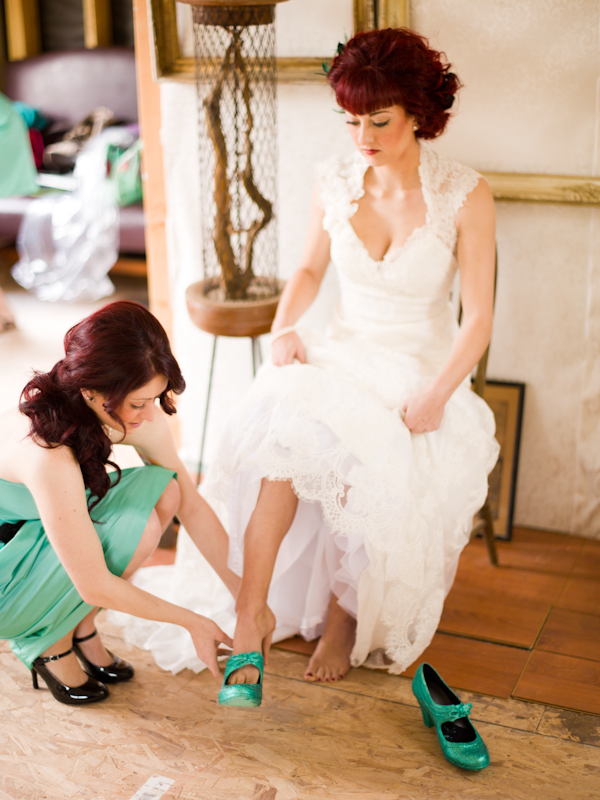 Bridesmaid helping bride put on green shoes