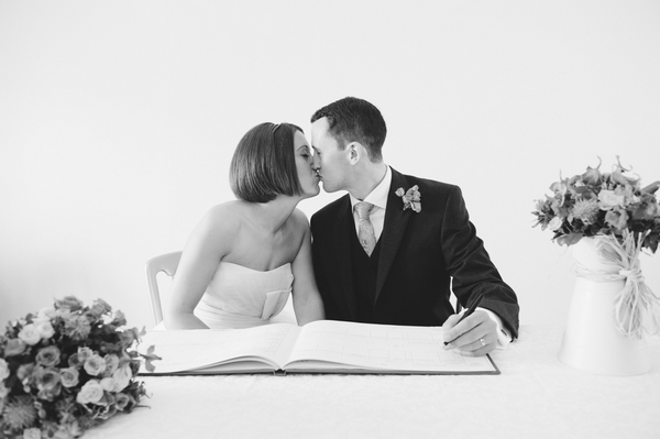 Bride and groom kissing whilst signing the register - Picture by Aaron Collett Photography