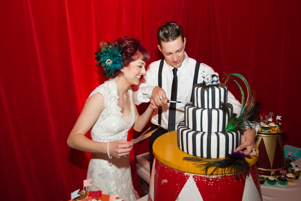 Bride and groom cutting black and white stripe cake
