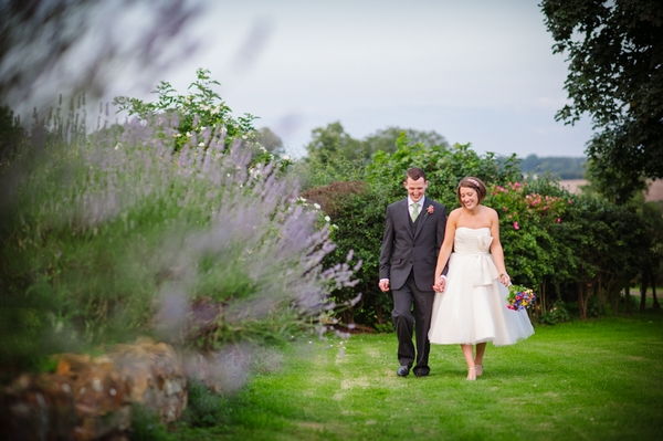 Bride and groom walking hand in hand through garden - Picture by Aaron Collett Photography