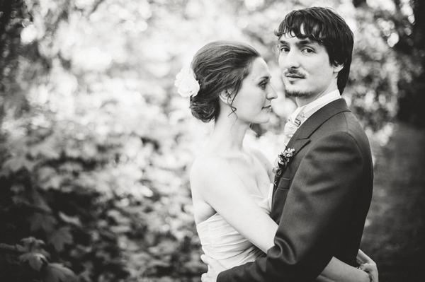 Black and white picture of bride with arms around groom's waist - Picture by Aaron Collett Photography