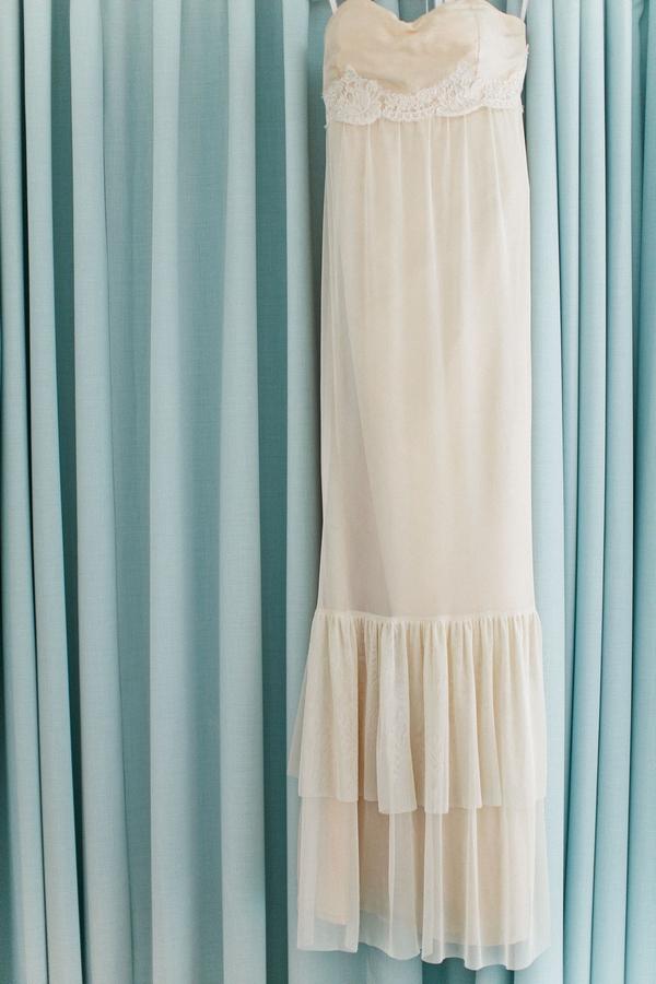 Wedding dress hanging over blue curtain