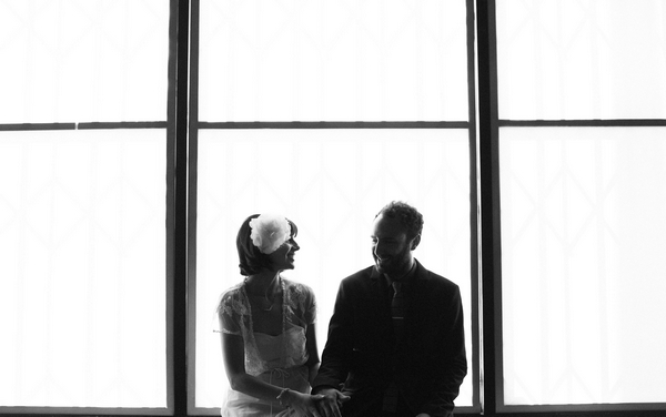 Bride and groom sitting in front of window