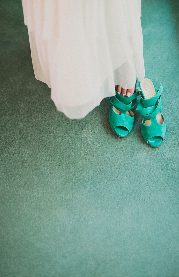 Bride putting on green wedding shoe