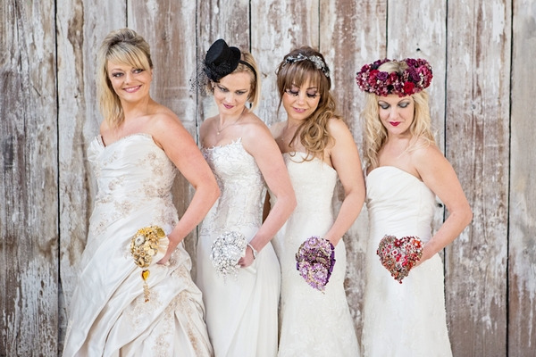 Four brides holding brooch bouquets