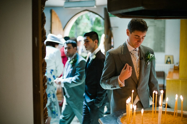Groom looking down at candles - Picture by Kristian Leven Photography