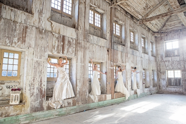 Brides standing in windows of warehouse