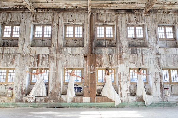 Four brides standing in windows of warehouse