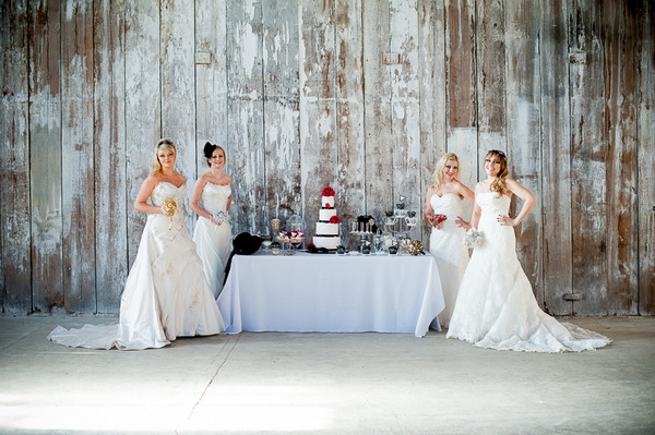 Brides standing by table of wedding cakes