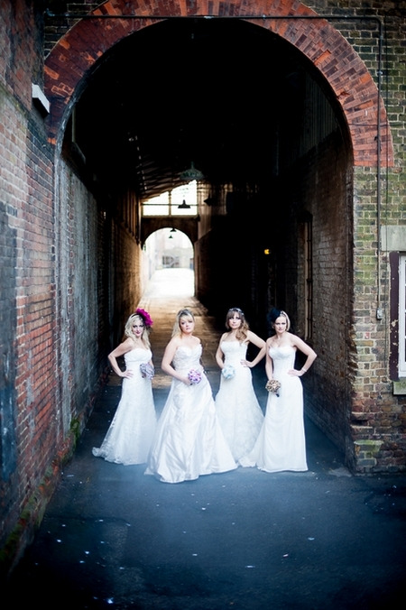 Four brides standing under arch