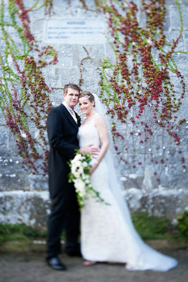 Bride and groom by wall
