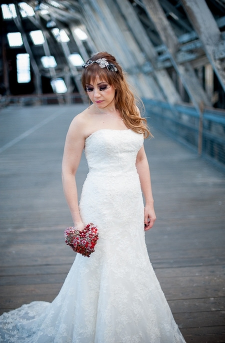 Bride looking down holding red brooch bouquet