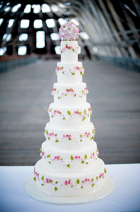 Tall white wedding cake with flower design