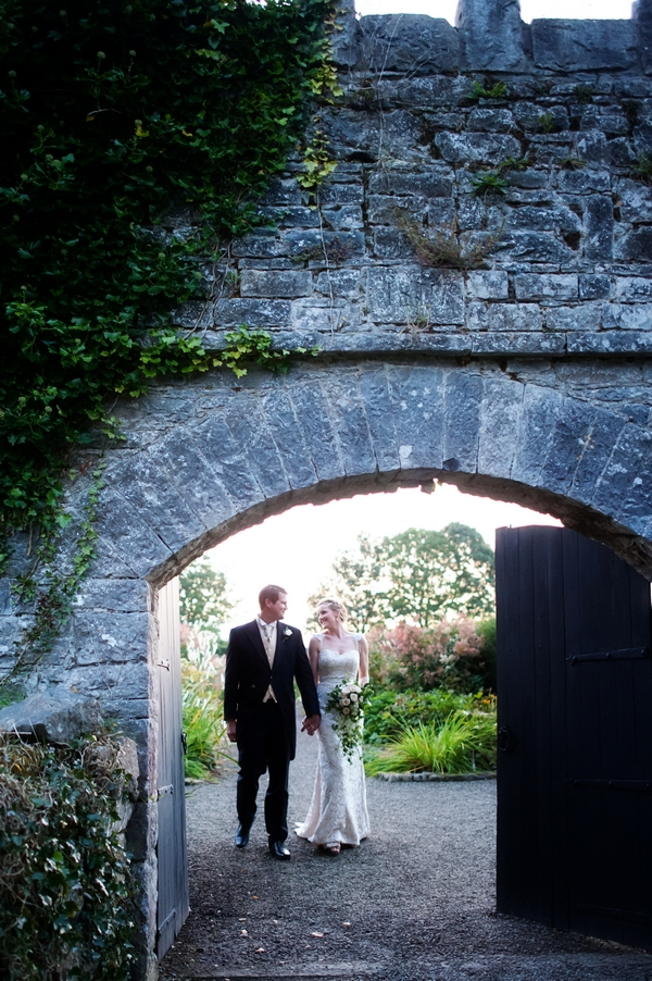 Bride and groom walking through castle grounds
