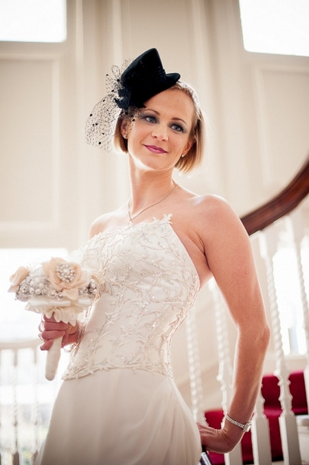 Bride with fascinator holding bouquet