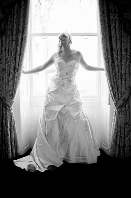 Bride standing in between curtains