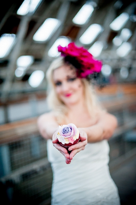 Bride holding out cupcake to camera