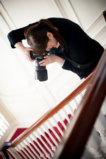 Photographer leaning over banister to take picture