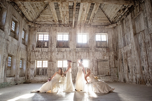 Four brides posing in warehouse