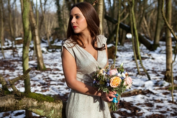 Bride in woods holding bouquet