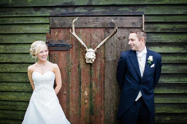 Bride and groom standing by animal skull on door