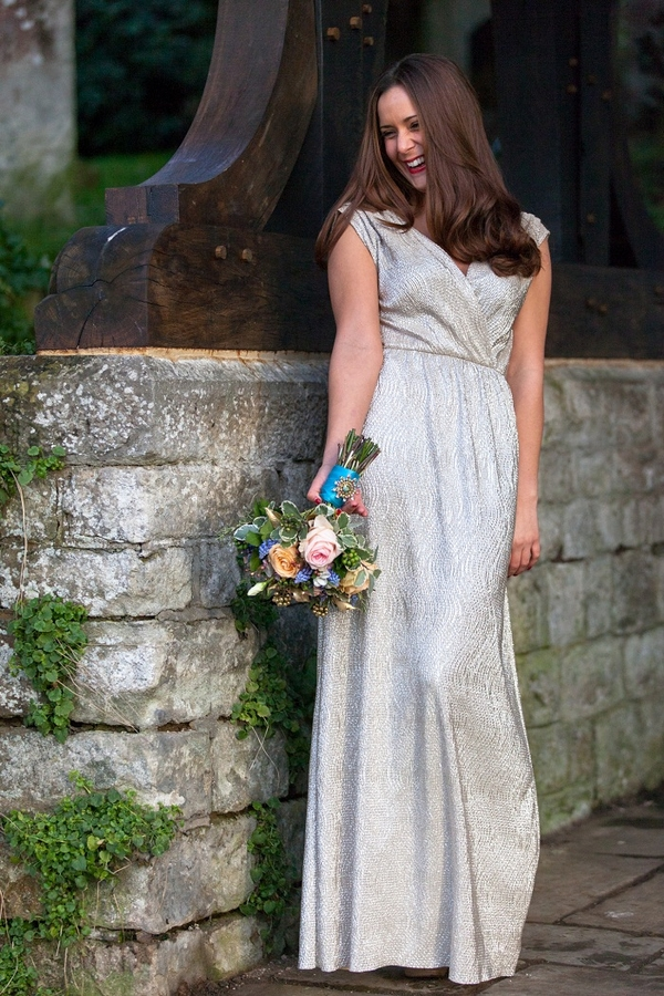 Bride standing next to wall holding bouquet
