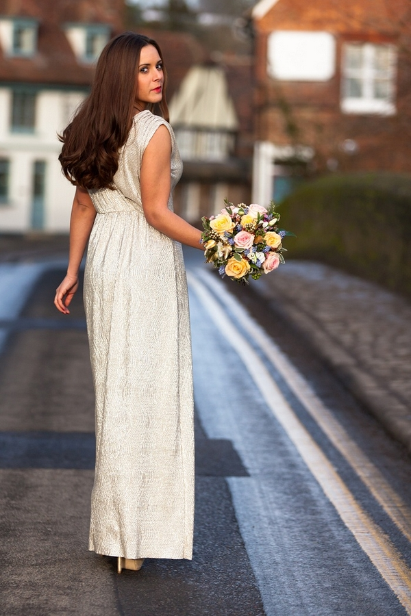 Bride in long dress walking down road