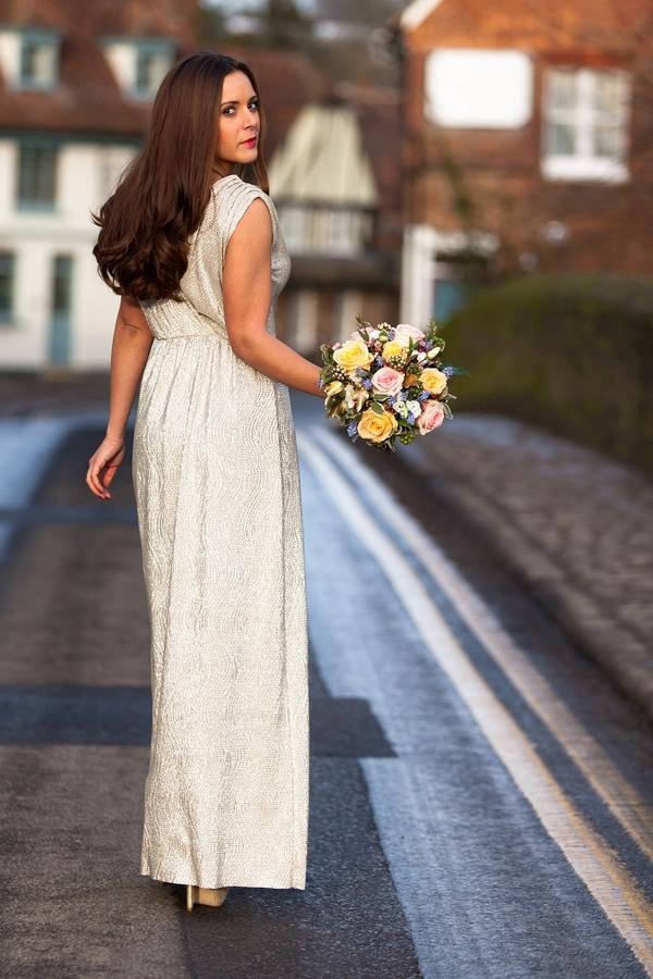 Bride in long dress walking down road