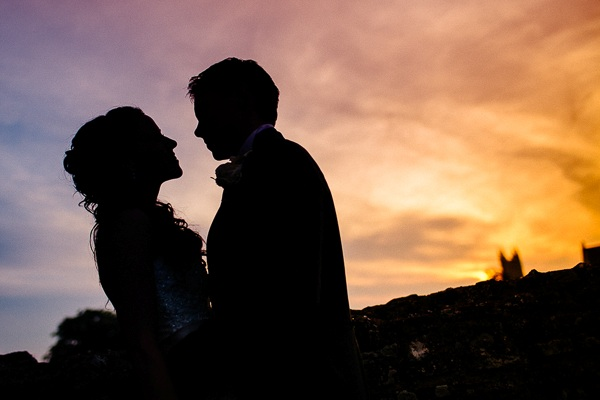 Bride and groom silhouette on colourful night sky