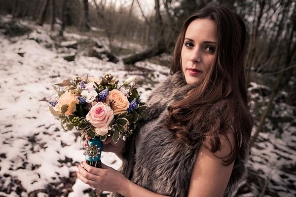 Bride wearing fur shrug, holding bouquet in woods