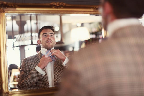 Groom looking in mirror doing up bow tie