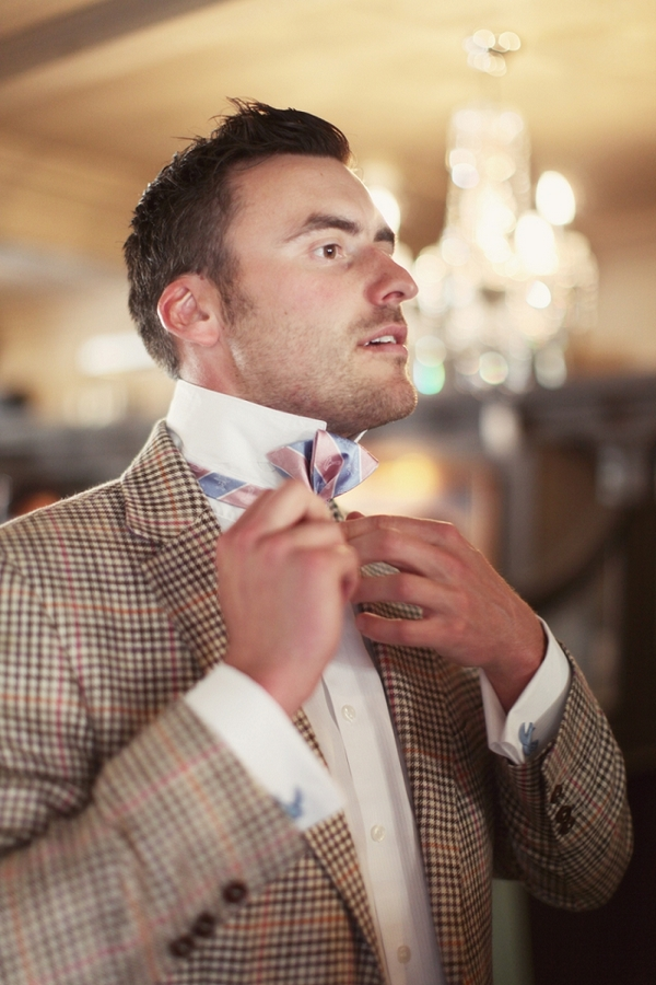 Groom doing up bow tie